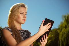 Woman sitting in park, relaxing and using tablet Royalty Free Stock Photography