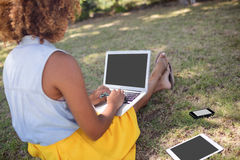 Woman sitting in park and using laptop. Rear view of woman sitting in park and using laptop on a sunny day Royalty Free Stock Photos