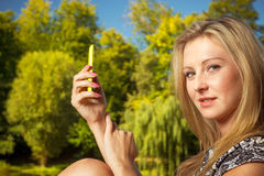 Woman sitting in park, using phone taking pictures Stock Photography