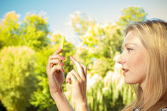 Woman sitting in park, using phone taking pictures Royalty Free Stock Photography