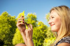 Woman sitting in park, using phone taking pictures royalty free stock photo