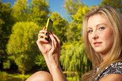 Woman sitting in park, using phone taking pictures royalty free stock photos