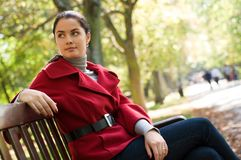 Woman sitting in a park on a wooden bench, Stock Photo