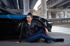 Woman sitting on the pavement next to the car Royalty Free Stock Photography