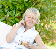 A woman sitting on phone with a drink Royalty Free Stock Photography
