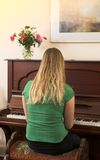 Woman Sitting at Piano Stock Images