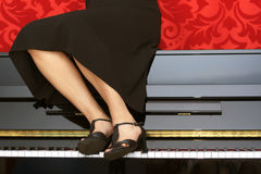 Woman sitting on a piano Royalty Free Stock Image