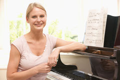 Woman sitting at piano Royalty Free Stock Images