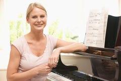 Woman sitting at piano Royalty Free Stock Images