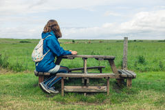 Woman sitting at picnic table in field Royalty Free Stock Photos