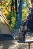 Woman sitting on picnic table outside tent on campsite on a crisp early fall morning. Woman sitting on picnic bench wearing hiking boots outside tent on campsite stock photography