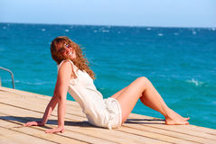 Woman is sitting on the pier. Beautiful woman sitting alone on the pier Stock Photo