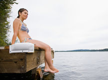 Woman sitting on pier. At lake Royalty Free Stock Images