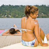 Woman sitting on pier applying sunscreen. Lotion Royalty Free Stock Photos
