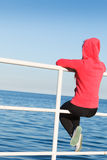Woman sitting on pier looking at horizon outdoors Stock Images