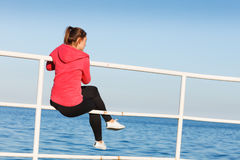 Woman sitting on pier looking at horizon outdoors Royalty Free Stock Image