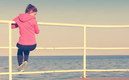 Woman sitting on pier looking at horizon outdoors Royalty Free Stock Photo