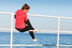 Woman sitting on pier looking at horizon outdoors Stock Photos