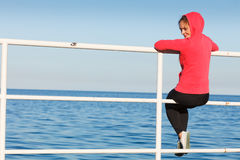 Woman sitting on pier looking at horizon outdoors Stock Image