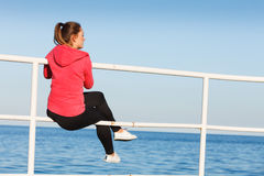 Woman sitting on pier looking at horizon outdoors Stock Photo