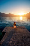 Woman sitting on the pier at sunrise. Lonely woman dreaming and looking at beautiful sunrise on the pier with sea and mountains on background. Back view, general Stock Photo