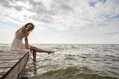 Woman sitting on pier at sunrise Royalty Free Stock Image