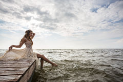 Woman sitting on pier at sunrise Royalty Free Stock Photo