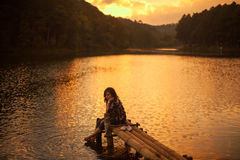 Woman sitting on a pier Royalty Free Stock Photography