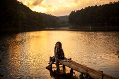 Woman sitting on a pier. Watching a stunning sunset Royalty Free Stock Image