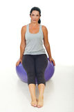 Woman sitting on pilates ball Stock Photography