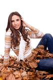 Woman sitting in a pile of autumn leaves Stock Images