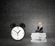 Woman sitting on pile of books, big alarm clock  right Stock Photo