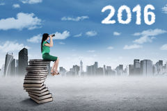 Woman sitting on the pile of books looking at sky Stock Photography