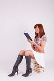 A woman is sitting on a pile of books and reads Stock Image