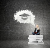 Woman sitting on a pile of books thinking about problem Royalty Free Stock Photo