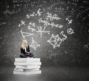 Woman sitting on a pile of books thinking about problem Royalty Free Stock Photos