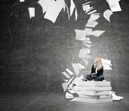 Woman sitting on a pile of books thinking about problem Stock Images
