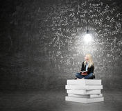 Woman sitting on a pile of books thinking about problem Royalty Free Stock Photography