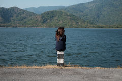 Woman sitting on pillar roadside front of her have big lake and Stock Image