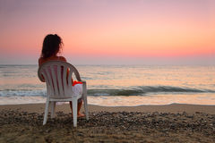 Woman sitting on plastic chair on beach Royalty Free Stock Image