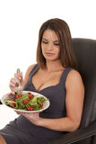 Woman sitting with a plate of salad Stock Images