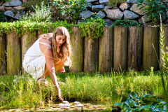 Woman sitting at pond in her garden Royalty Free Stock Photos