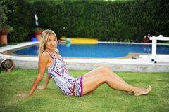 Woman sitting by pool Royalty Free Stock Images