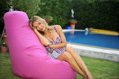 Woman sitting by pool Stock Image