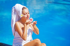 Woman sitting beside a pool stock images