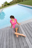 Woman sitting on pool deck. Woman sitting by pool after exercising Royalty Free Stock Images
