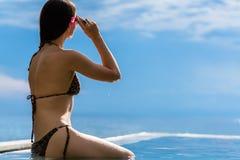 Woman sitting on pool rim looking at ocean Royalty Free Stock Photo