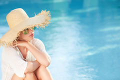Woman sitting by the pool side and smiling over her s Royalty Free Stock Photo