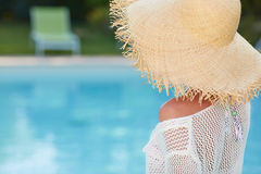 Woman sitting by the pool side and smiling over her s Royalty Free Stock Image