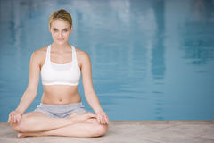 Woman sitting poolside doing yoga. Smiling Stock Photography